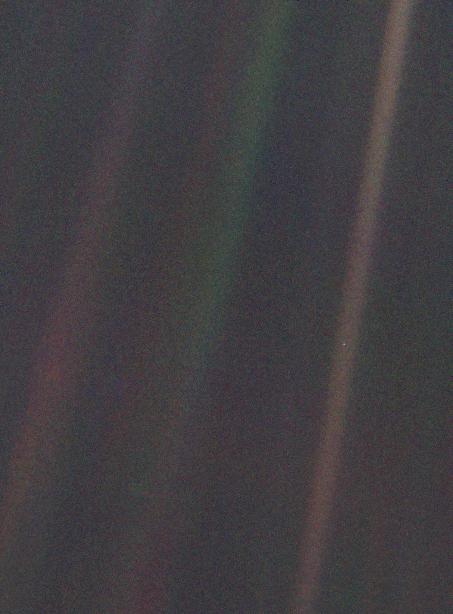زمین از فاصله ۶ میلیارد کیلومتری (۳٫۷ میلیون مایل) همانند یک نقطه کوچک به نظر میرسد (لکه بسیار کوچک سفید در میانه پایین تصویر، سمت راست در میانه نوار قهوهای) در اعماق تاریکی فضا